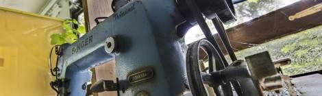 Transmission du moteur de la machine à coudre Singer venant du moteur situé sous la table.