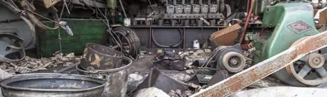 Compartiment moteur d'une casse en cours de destruction à la casse. Les hydrocarbures sont partout et coulent sur le sol....