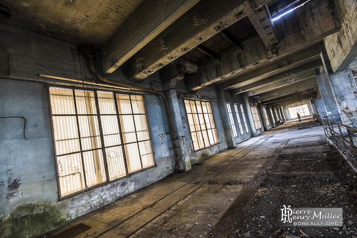 Couloir obscure avec baies vitrées diffusant de la lumière à la centrale EDF