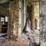 Bâtiment en friche avec moisissure sur les murs et porte défoncée