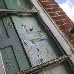 Fenêtre et volets en bois avec peinture écaillée au château de Bonnelles