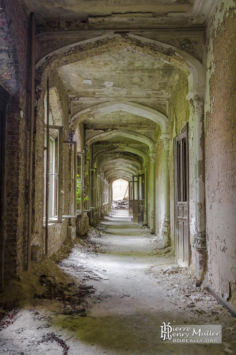 Couloir avec ambiance rose et vert dans le château de Mesen