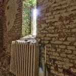 Pièce délabrée avec radiateur en fonte et fenêtre au château Noisy en HDR