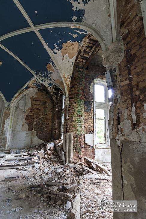 Plafond avec voûte en croisée d'ogive bleu et murs mangé par la mérule
