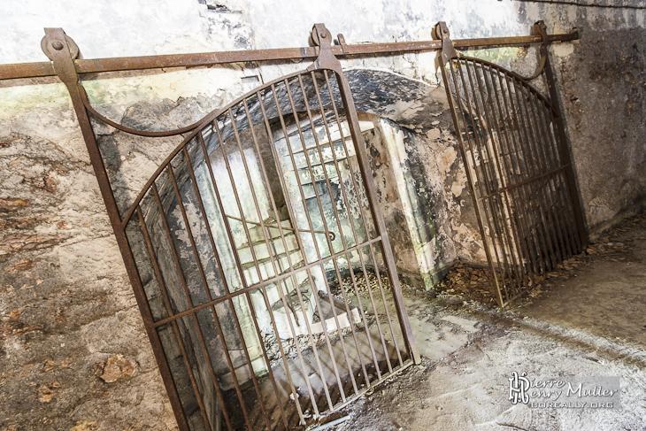 Double porte coulissante métallique fermant l'accès à un escalier