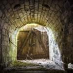 Sortie du tunnel fermée par une porte en bois laissant passer la lumière
