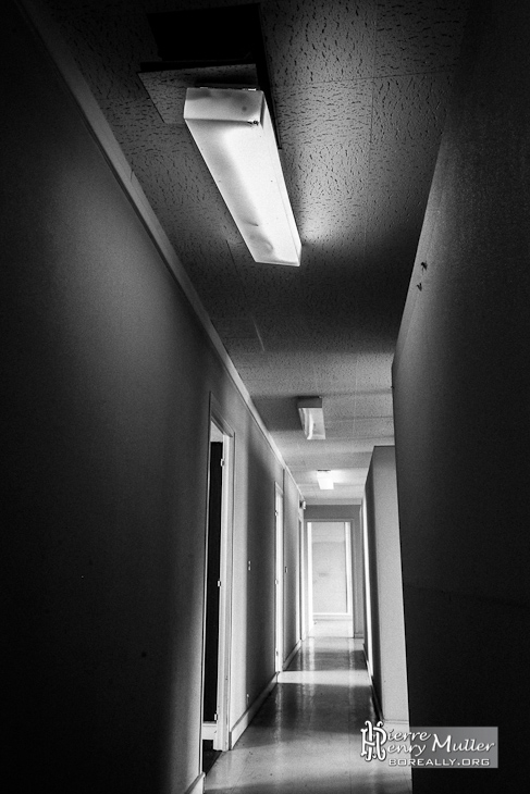 Photo noir et blanc d'un couloir éclairée aux néons de l'imprimerie abandonnée