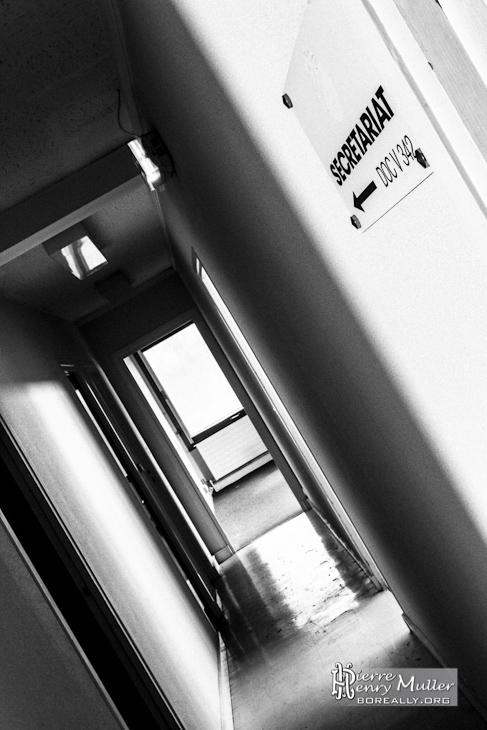Photo noir et blanc d'une plaque d'orientation du secrétariat de l'imprimerie abandonnée