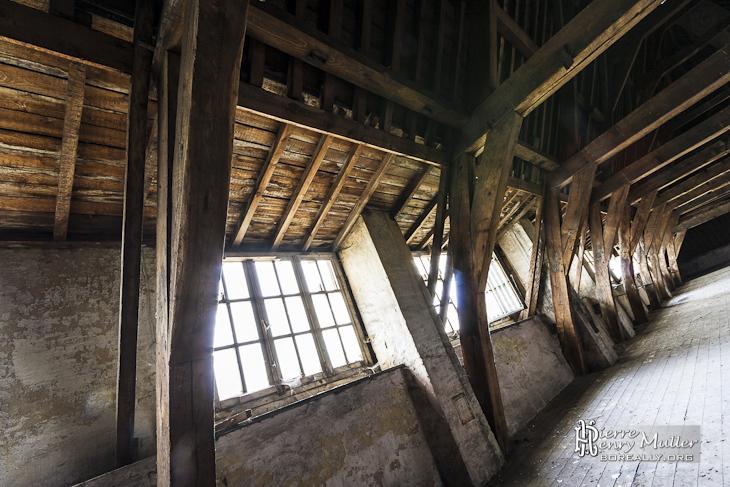 Fenêtres sous les toits avec la charpente en bois du monastère abandonné