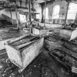 Berlines sur rails dans un hangar de la papeterie Darblay en noir et blanc