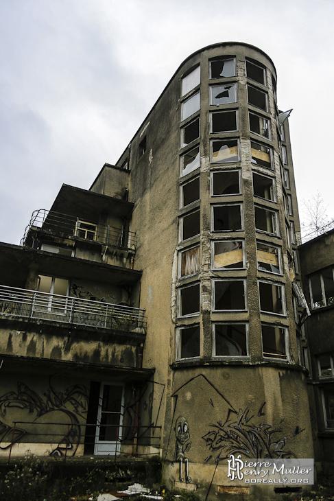 Cage d'escalier arrondie avec vitres carrées et les différents niveaux de balcons