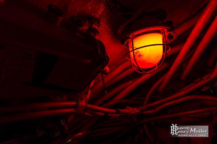 Eclairage rouge dans le sous-marin russe au milieu des câbles