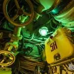 Lampe verte au milieu des câbles et vannes du sous-marin