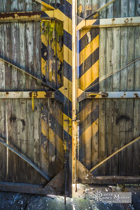 Porte en bois peinte en jaune et noir du dépôt de trains