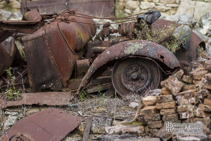 Epave de voiture rouillée dans le village