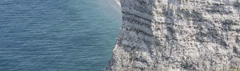 La plage et la ville d'Etretat vue depuis la porte d'Aval avec au premier plan des personnes sur le chemin des falaises....