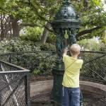 Enfant remplissant une gourde d'eau à la fontaine Wallace de la butte Montmatre