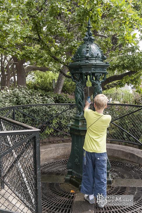 enfant remplissant une gourde d 39 eau la fontaine wallace de la butte montmatre boreally. Black Bedroom Furniture Sets. Home Design Ideas
