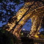Pieds de la Tour Eiffel et reflet sur le plan d'eau de nuit