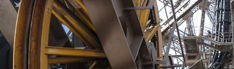 ...Au premier plan une roue jaune de machinerie d'ascenseur et au second plan en noir les guides d'ondes radio. Ces feeders sont des liaisons coaxiale reliant les antennes du somme de la Tour Eiffel à la station d'émission situé sous et à proximité de la tour....