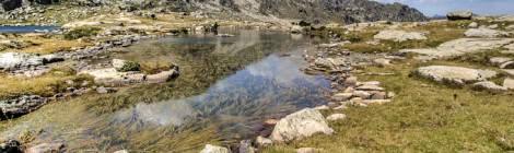 Photo TTHDR d'un paysage de montagne avec un lac, un ciel bleu et quelques nuages....