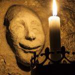 Visage souriant modelé au mur devant une bougie