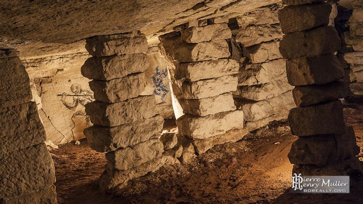 Dessins sur les murs de la carrière au travers des piliers à bras
