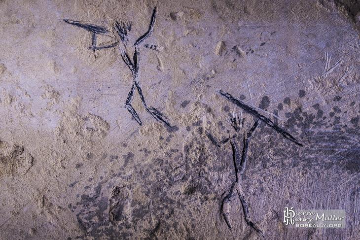 Dessin préhistorique de chasseurs sur les murs de la carrière