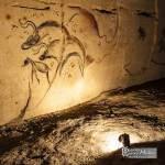 Fresque préhistorique reconstituée éclairée par une lampe acétylène