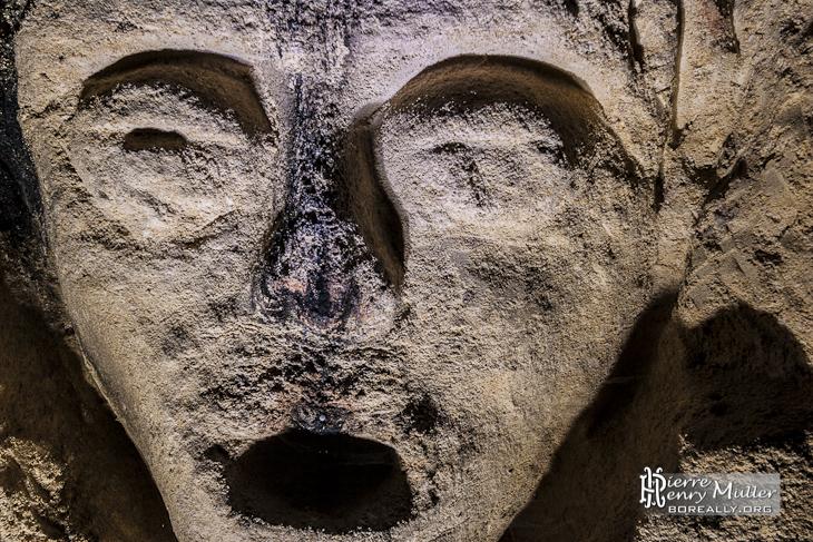 Sculpture d'un visage sur un mur de calcaire dans la carrière patate