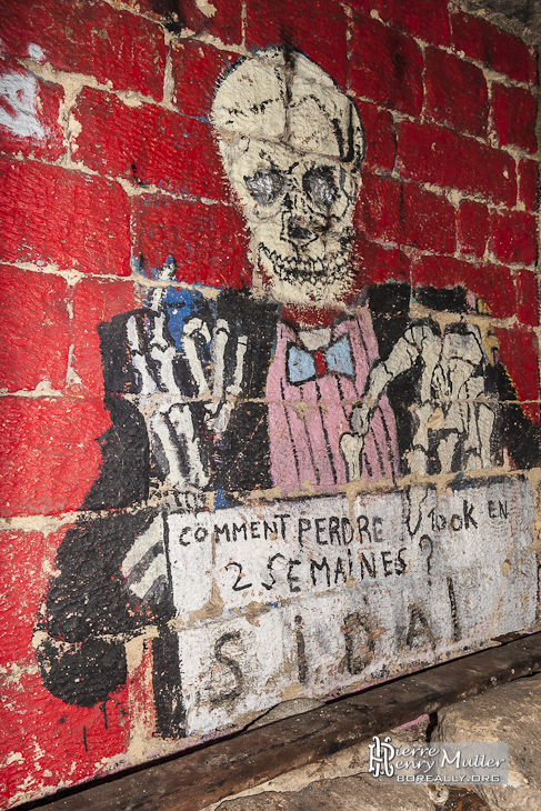 Squelette habillé d'un costume sur le mur des promotions des catacombes de Paris