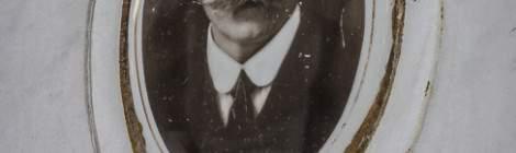 ...Sur la stèle d'une tombe, une photo d'un homme avec moustache et l'inscription «Ici repose …»...