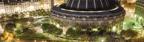 Vue depuis les toits sur la Bourse du Commerce de Paris et sa coupole illuminée ainsi que les jardins de la dalle des Halles de nuit.