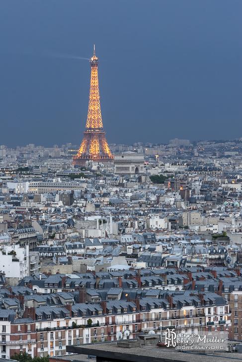 Tour Eiffel et Arc de Triomphe sous un ciel orageux