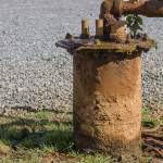 Canalisation rouillée sortant de terre dans une installation pétrolière